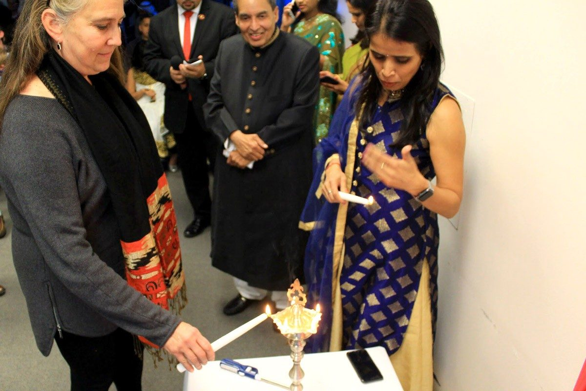 Business information technology professor Barbara Hoopes participates in the lamp lighting ceremony, which marks the beginning of the event, while hospitality and tourism management professor Mahmood Khan and MBA student Mala Lal look on.