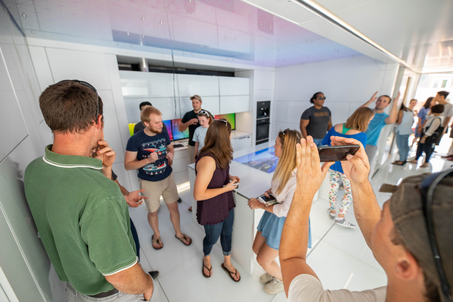 A man holding a smartphone holds it up to take a picture of the house, which is white inside with some colorful electronic displays. There is a crowd of people standing inside the house.