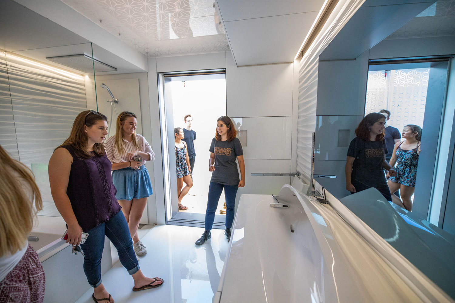 Three women stand inside a futuristic-looking bathroom, complete with a 3D printed sink.