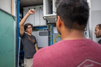Matt Erwin, a senior from Chesapeake, Virginia, studying computer engineering, shows FutureHAUS Dubai visitors some of the electrical components inside one of the home's signature cartridges. (Photo by Erica Corder)