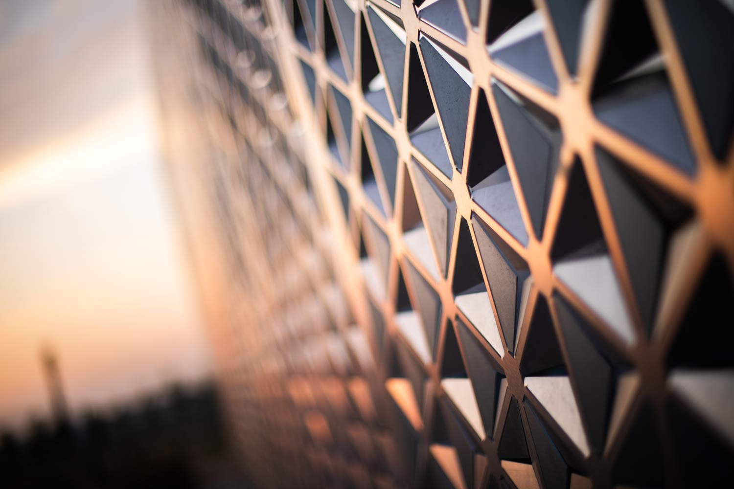 Vivid orange light paints a screen wall that is cut with an intricate pattern.