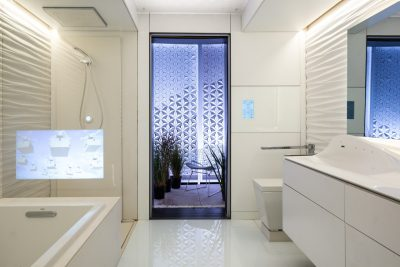 The FutureHAUS' full bathroom, which boasts actuators that can raise and lower the vanity and toilet. A sensor embedded in the glass floor can detect if occupants slip and fall, and can send alerts in an emergency. (Photo by Erik Thorsen)