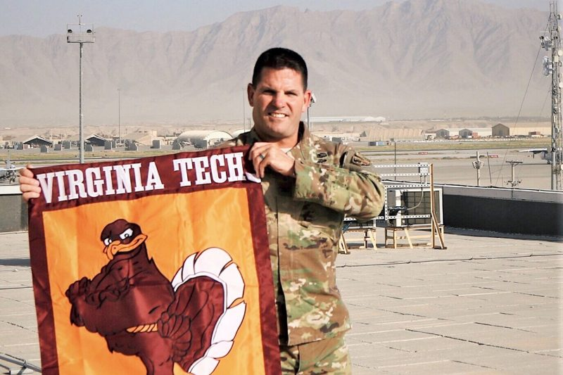 "U.S. Army Col. Barry ""Chip"" Daniels holds a Virginia Tech flag while deployed to Afghanistan."
