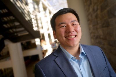 Andrew Luo poses in the atrium of Pamplin Hall.