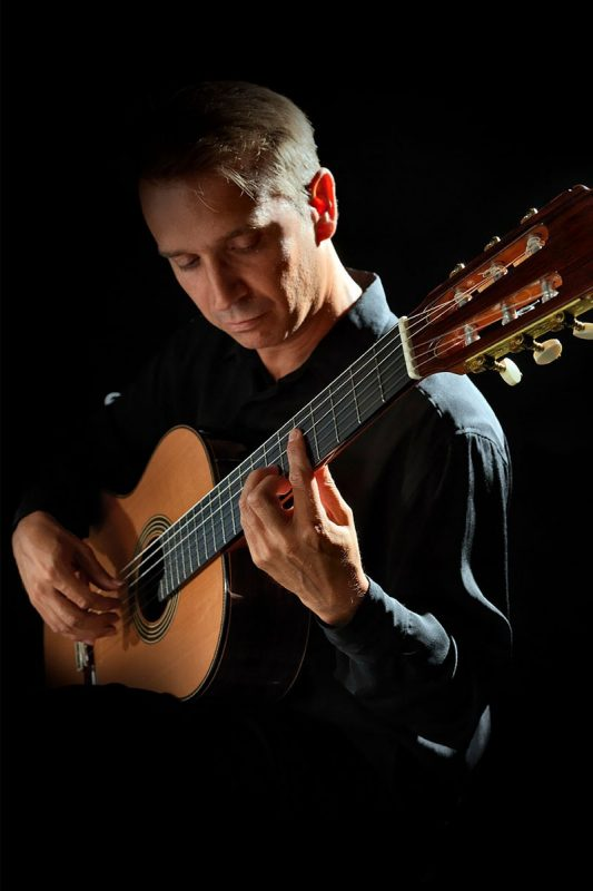 Professor Nicolau playing classical guitar.