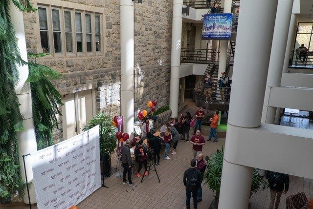 Giving Day ambassadors prepare for an influx of students in the Pamplin Hall atrium.
