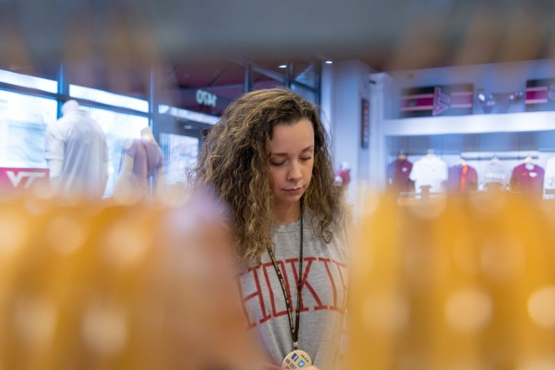 Multimedia journalism major Courtney Flickinger arranges a display at Alumni Hall, the store she works at in Blacksburg. Photo by Olivia Coleman for Virginia Tech.